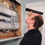 Jamie Ruth of Baseline Inspections checking the electrical panel of a house during a pre-purchase inspection.