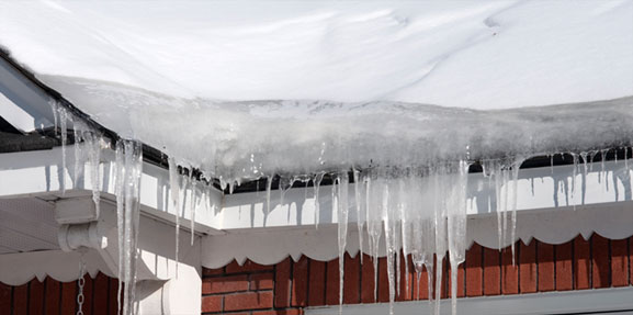 Icicles forming an ice dam on the roof of a house in the Winter.