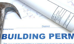 Hammer and blueprint with the words Building Permit placed as an overlay.