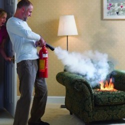 Person putting out a couch fire with a fire extinguisher in their home while another person watches in shock.