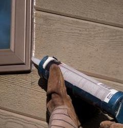 Person putting new silicone caulking on exteriors of window frames as part of their Springtime home maintenance.